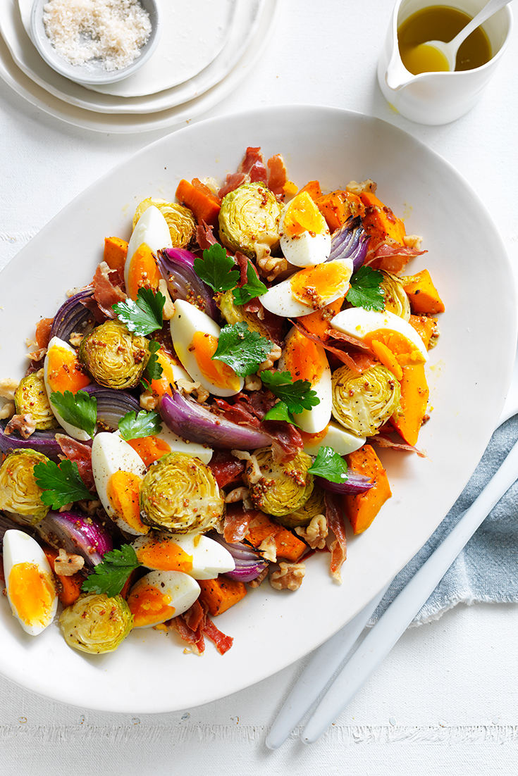 This colourful roasted pumpkin, Brussel sprouts and prosciutto with egg recipe is a great winter salad to serve to a crowd.